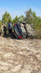 Car rolled over on its side in the trees